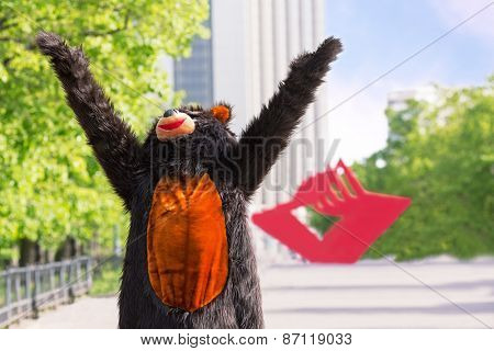 actor dressed as bear enjoys the sun on avenue of park on background of red stars