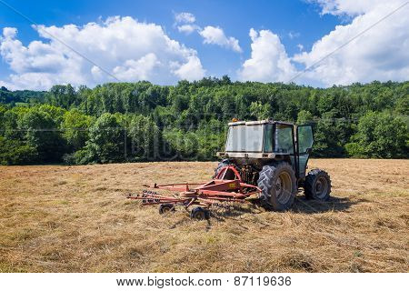 Tractor With Rotary Rakes Parked On Dry Grassland
