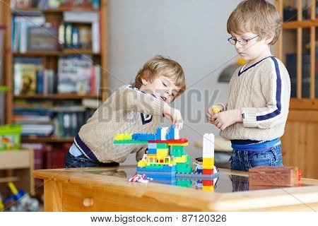 Two Little Kid Friends Playing With Lots Of Colorful Plastic Blocks