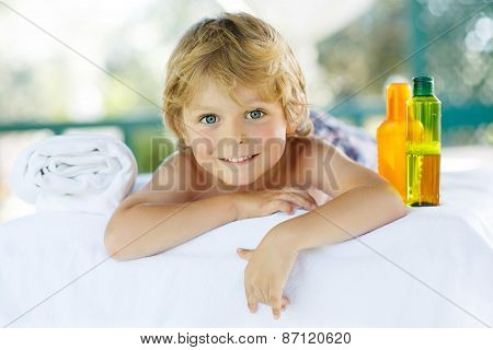 Adorable Little Blond Kid Relaxing In Spa With Having Massage