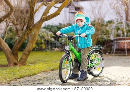Little Preschool Kid Boy Riding With His First Green Bike