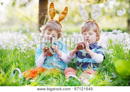 Sibling Boys In Easter Bunny Ears Eating Chocolate