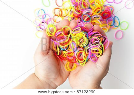 Little Child Hands And Pile Of Colorful Rubber Bands