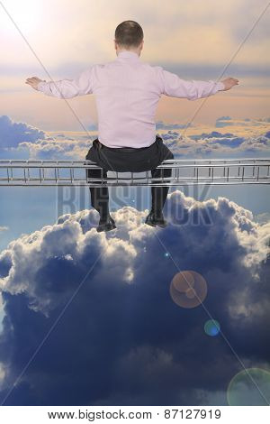 Businessman sitting on light metal girder beam over cloud sky in background