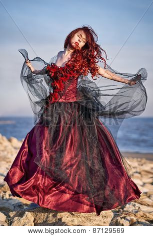 Beautiful Young Woman In Red Dress Standing On Sea Shore
