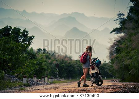 Young lady standing by her motorbike and enjoying landscape view