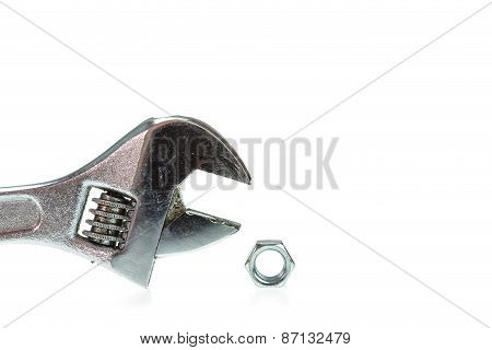 Adjustable Wrench With Nut Isolated On White
