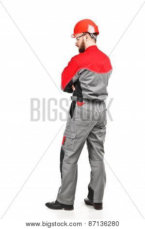 Rear View Of Man Wearing Overalls With Red Helmet