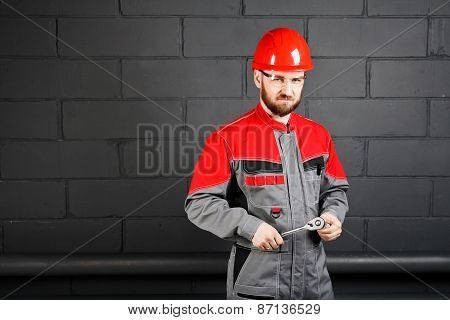 Man Wearing Overalls With Red Helmet And Wrench Near Brick Wall