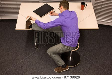 healthy lifestyle at work - business man writing on paper stretching leg,sitting on pneumatic stool in his office