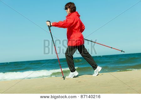 Nordic Walking. Woman Hiking On The Beach.