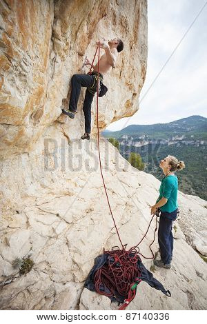 Climber going to clip rope at beginning of route