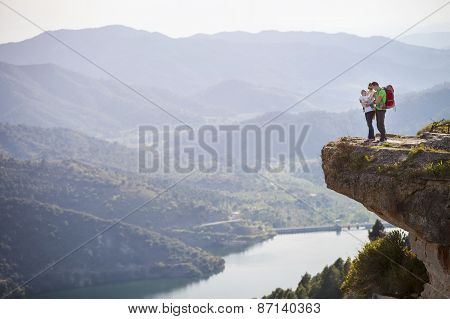 Happy couple with little son standing on cliff