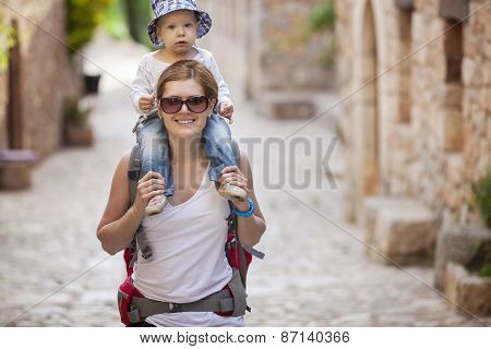 Caucasian woman tourist carrying her little son