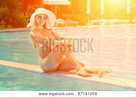 Beautiful female in white bikini seating near the waterpool under sun light