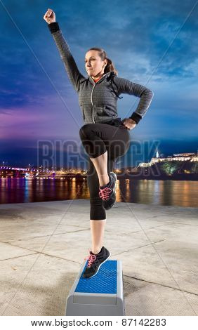 Fit woman exercising on stepper
