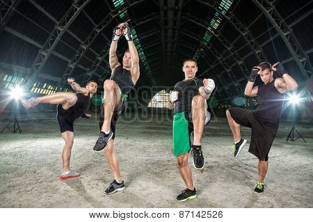 Four men practicing kick boxing, making hit with legs