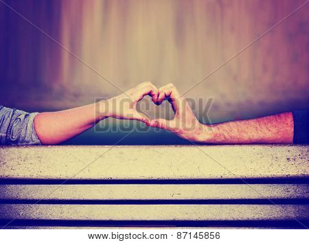 two people making a heart shape with their hands on a bench toned with a retro vintage instagram filter  app or action (shallow depth of field on the thumbs)