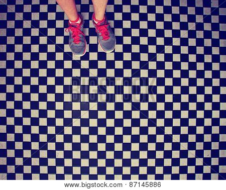 an overhead photo of a pair of tennis shoes on a grungy dirty checkered tile floor toned with a retro vintage instagram filter app or action