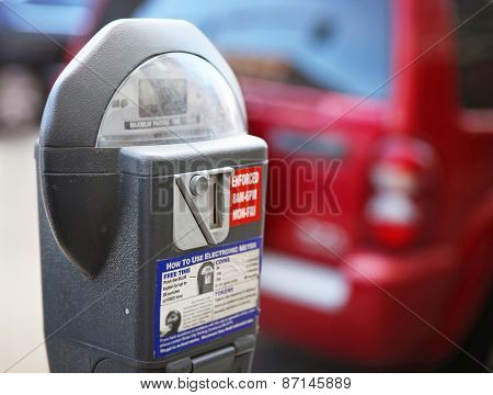 a parking meter with a car in the background on a city street downtown