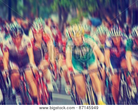blurred image of a pack of bicycle riders rounding a corner toned with a retro vintage instagram filter effect app or action