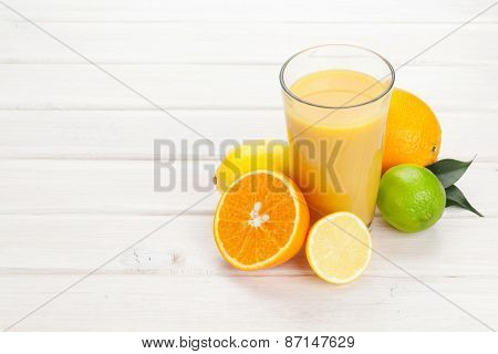 Orange juice and citrus fruits on white wooden table with copy space