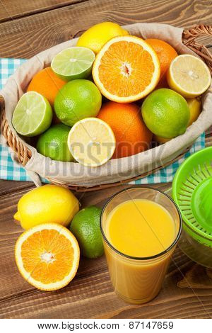 Citrus fruits and glass of juice. Oranges, limes and lemons. Top view over wood table background