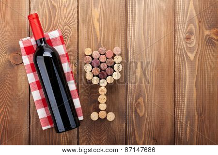 Red wine bottle and glass shaped corks. View from above over rustic wooden table background