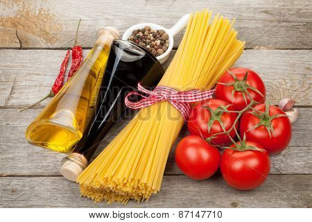 Pasta, tomatoes, condiments and spices on wooden table background