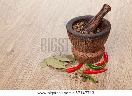 Mortar and pestle with red hot chili pepper and peppercorn on wooden table