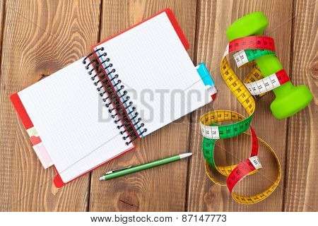 Dumbells, tape measure and notepad for copy space. Fitness and health