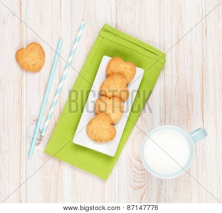 Cup of milk and heart shaped cookies on white wooden table