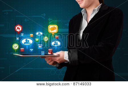 Young girl presenting a tablet with colorful social icons and signs