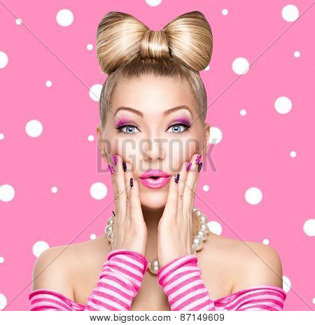 Beauty Surprised fashion model girl with funny bow hairstyle, pink nail art and makeup over polka dots background. Colourful Studio Shot of Funny Woman. Vivid Colors. Emotion