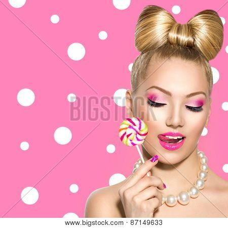 Beauty fashion model girl Eating colourful lollipop. Young funny woman with bow hairstyle, pink nail art and makeup over polka dots background. Sweet candy