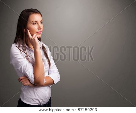 Beautiful young woman thinking with empty copy space