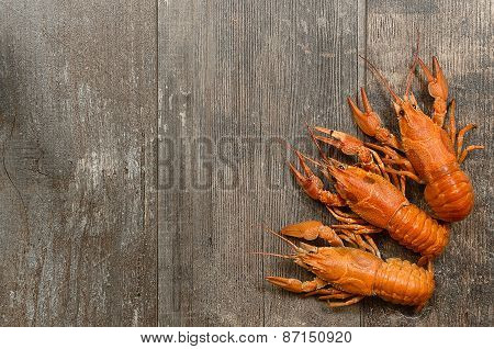 Three Red Crayfishes In The Left-bottom Corner On Old Wooden Table