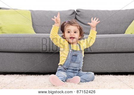 Playful baby girl sitting on the floor next to a modern sofa and gesturing happiness isolated on white background