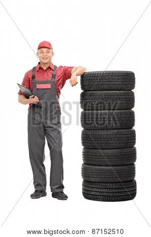 Full length portrait of a young male mechanic in a gray jumpsuit leaning on a stack of tires and holding a clipboard isolated on white background