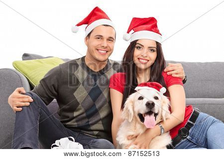 Studio shot of a young couple and their dog wearing Santa hats and celebrating Christmas seated on the floor next to a modern grey sofa isolated on white background