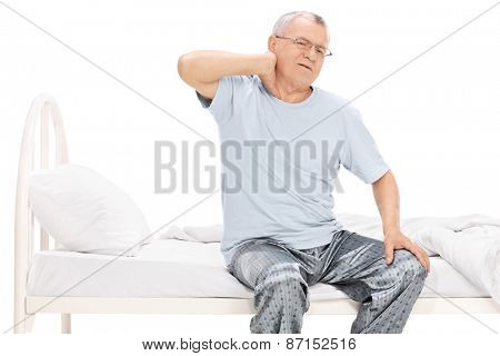 Senior man in pajamas feeling pain in his neck seated on a bed isolated on white background