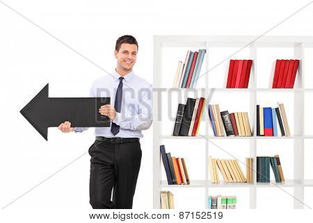 Cheerful young guy holding a big black arrow pointing right and leaning on a white bookshelf isolated on white background