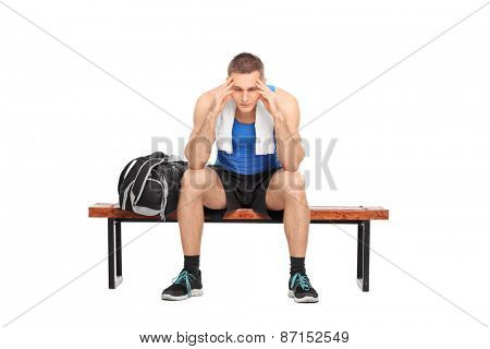 Worried young man in sportswear sitting on a wooden bench, looking down and wondering, isolated on white background