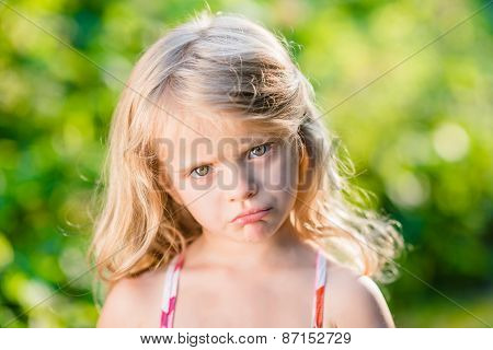 Close-up Portrait Of Displeased Blond Little Girl With Pursed Lips