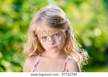 Close-up Portrait Of Sad Blond Little Girl With Pursed Lips. Sunny Summer Day In Beautiful Park