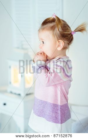 Amazed Blond Little Girl With Ponytail Staying On Bed And Keeping Her Hands In Her Mouth