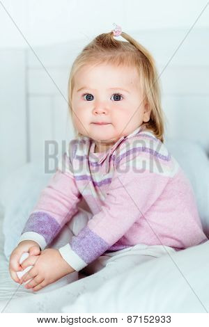 Cute Blond Little Girl With Big Grey Eyes And Plump Cheeks Sitting On Bed In Bedroom
