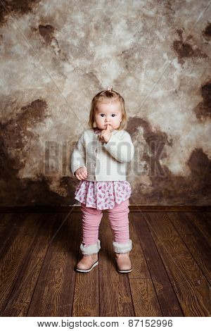 Blond Little Girl With Big Grey Eyes And Plump Cheeks Staying And Keeping Her Finger In Her Mouth