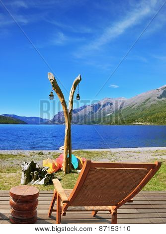 The original boathouse. Column with lights and next to him on the ground dries colorful boats. Front of the station - a wooden lounger. The lake with the cold blue water and grassy bank