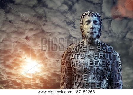 Metal human statue covered with letters